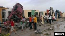 Warga berdiri di luar rumah-rumah mereka yang rusak akibat hantaman mobil yang dibawa tornado di kota Ciudad Acuna, negara bagian Coahuila, Meksiko (25/5). (Reuters/Ramiro Gomez)