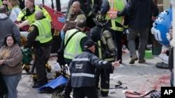 Petugas medis membantu orang-orang yang cedera di dekat garis finish Boston Marathon 2013, Copley Square, Senin, 15 April.