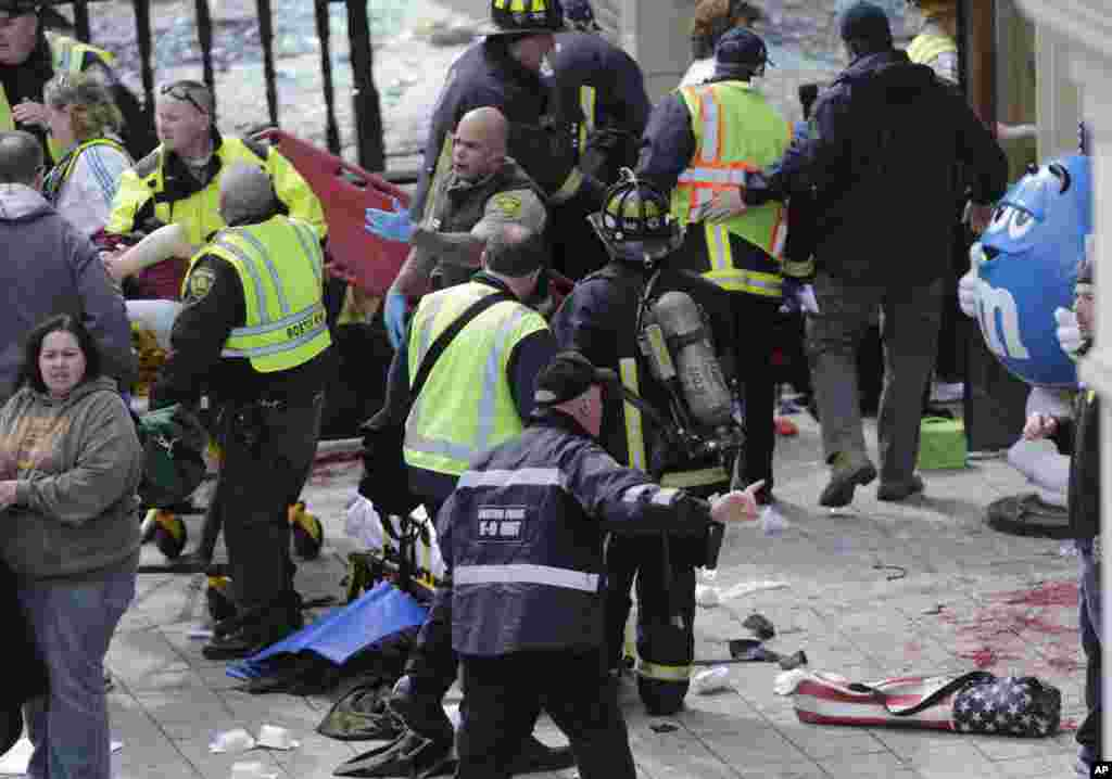 Medical workers aid injured people at the finish line of the 2013 Boston Marathon following an explosion, April 15, 2013.