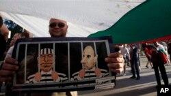 Người biểu tình cầm ảnh vẽ cựu thủ tướng Boyko Borisov và phó chủ tịch đảng của ông sau song sắt trong cuộc biểu tình phản đối đảng GERB ở Sofia, 11/5/13