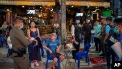 Petugas memberitahu pemilik bar untuk sementara tutup dalam upaya mencegah meluasnya perebakan virus corona di Khao San Road, Bangkok, Thailand, 18 Maret 2020. (Foto: dok).