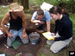 Colin Grier (center) discusses a find with graduate students Chris Arnett (left) and Kelly Derr (right).