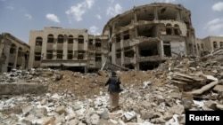 A Houthi militant walks in front of a government compound, destroyed by recent Saudi-led air strikes, in Yemen's northwestern city of Amran July 27, 2015.