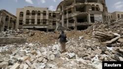 Một chiến binh Houthi đi phía trước đống đổ nát bị phá hủy bởi các cuộc không kích do Ả rập Xê út dẫn đầu tại Amran, thành phố tây bắc Yemen, hôm 27/7/2015.
