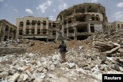 FILE - An Iranian-allied Houthi militant walks in front of a government compound, destroyed by recent Saudi-led airstrikes, in Yemen's northwestern city of Amran, July 27, 2015.