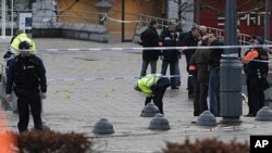 Police stand next to evidence markers after an incident in Liege, Belgium, December 13, 2011.