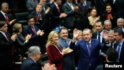 FILE - Turkey's Prime Minister Tayyip Erdogan greets his supporters in parliament.