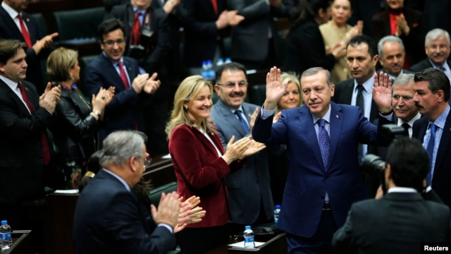 Turkey's Prime Minister Tayyip Erdogan greets his supporters as he arrives at a meeting at the Turkish parliament in Ankara, Feb. 18, 2014.