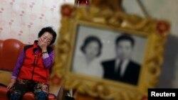 1972년 남편이 납북된 여성이 애써 울음을 참고 있다. 거실에 부부의 결혼 사진을 걸려있다. 납북되었다가 40여년 만에 귀환한 납북 선원 소식이 알려진 지난 10월 당시.
