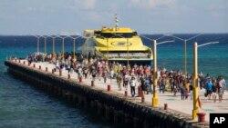 Turistas desembarca de un ferry en el muelle de Playa del Carmen, cerca de Cancún, México.