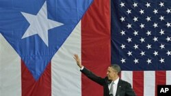 President Barack Obama waves to a crowd gathered inside a hangar at the Muniz Air National Guard Base, shortly after his arrival in San Juan, Puerto Rico, June 14, 2011