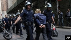Police officers take away a protester during an Occupy Wall Street march at the New York Stock Exchange in Manhattan, Sept. 17, 2012.