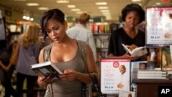 Mya (Meagan Good) grabs a copy of Steve Harvey's book in Screen Gems' comedy THINK LIKE A MAN