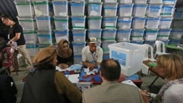 Afghan election commission workers sort ballot papers for an audit of the presidential run-off votes at an election commission office in Kabul, Aug. 3, 2014.