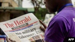 A man reads the front page of a special edition of The Herald newspaper about the crisis in Zimbabwe with the headline 'No military takeover - ZDF' on Nov. 15, 2017 in Harare.