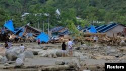 Warga memeriksa rumah-rumah mereka pasca banjir dan tanah longsor di Sentani, Papua Minggu 17/3 (Foto. Antara/Gusti Tanati via Reuters).