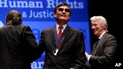 Chinese human rights activist Chen Guangcheng, center, smiles after being awarded the 2012 Tom Lantos Human Rights Prize by actor Richard Gere, right, on Capitol Hill in Washington, Jan 29, 2013.