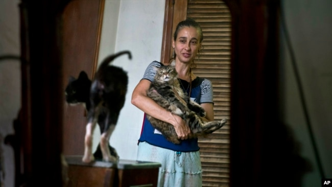 Grettel Montes de Oca Valdes, a professional dancer and founder of the group Cubans in Defense of Animals poses with cats in her home in Havana, Cuba, April. 4, 2019. A group of animal-lovers will march down one of Havana's main thoroughfares Sunday calling for an end to animal cruelty in Cuba.