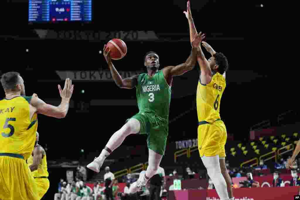 Nigeria's Caleb Agada (3) drives to the basket against Australia's Josh Green (6) during a men's basketball preliminary round game at the 2020 Summer Olympics, Sunday, July 25, 2021, in Saitama, Japan. (AP Photo/Eric Gay)