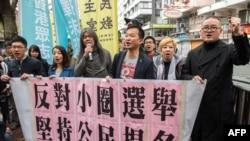 Aktivis Raphael Wong (tiga dari kanan) dari Liga Sosial Demokratik dan peserta unjuk rasa Gerakan Payung Shiu Ka-chun (kanan) bergabung bersama para demonstran lainnya menuju lokasi pemilihan Eksekutif Hong Kong, 26 Maret 2017 (Foto: AFP).