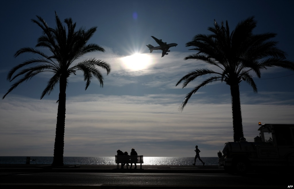 People look at an Airbus 380 plane flying toward the airport of the southern French city of Nice.