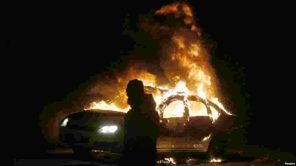 A car burns on the street after a grand jury returned no indictment in the shooting of Michael Brown in Ferguson, Missouri, Nov. 24, 2014.