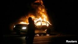 Một chiếc xe bị đốt cháy trên đường phố tại Ferguson.