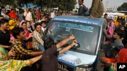 Bangladeshi garment workers vandalize a vehicle during a protest in Savar, on the outskirts of Dhaka, Bangladesh, Jan. 9, 2019.