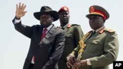 FILE - South Sudan's President Salva Kiir, left, accompanied by army chief of staff Paul Malong, right, waves during an independence day ceremony in the capital Juba, July 9, 2015.