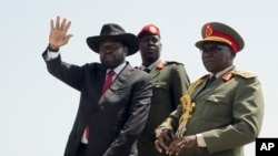 FILE - South Sudan's President Salva Kiir, left, accompanied by army chief of staff Paul Malong, right, waves during an independence day ceremony in the capital Juba, South Sudan.