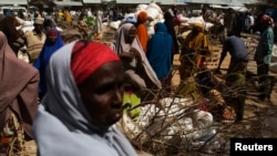 Somali refugees organize their collected ration of food during a distribution exercise outside a United Nations World Food Programme (WFP) centre in Dagahale, one of the several refugee settlements in Dadaab, Garissa County, northeastern Kenya, October 8, 2013.