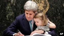 바락 오바마 미 대통령을 대신해 서명식에 참석한 존 케리 국무장관이 자신의 손녀를 안고 파리기후변화협정에 서명하고 있다.
