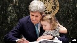 El secretario John Kerry acompañado de su nieta firma el histórico acuerdo sobre cambio climático en la sede de Naciones Unidas.
