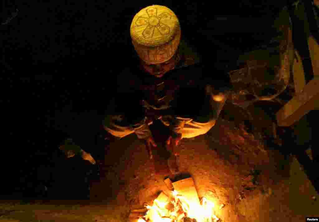 A Pakistani child burns trash to keep himself warm on Saddar Road in Peshawar.