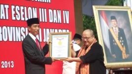 Gubernur Jakarta Joko Widodo menerima penghargaan dari Jaya Suprana dari Museum Rekor Indonesia (MURI) berkat upacara pelantikan massal camat dan lurah. (VOA/Iris Gera)