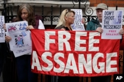 Supporters of WikiLeaks founder Julian Assange stand outside the Ecuadorean Embassy as Assange addresses the media, in London, May 19, 2017.
