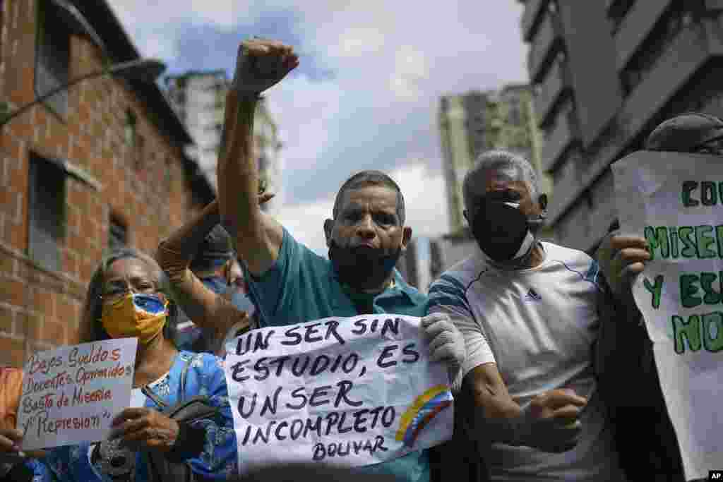 """A man shouts slogans as he holds the Spanish quote: """"An uneducated person is an incomplete person. Bolivar."""" at a demonstration by teachers demanding better salaries in Caracas, Venezuela, on World Teachers' Day, Monday, Oct. 5, 2020, amid the COVID-19 pandemic. (AP Photo/Matias Delacroix)"""