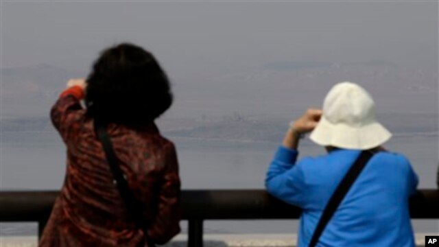 Visitors watch North Korean side at unification observation post near the border village of Panmunjom, north of Seoul, April 1, 2014.