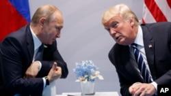 도널드 트럼프(오른쪽) 미국 대통령과 블라디미르 푸틴 러시아 대통령이 지난달 7일 독일 함부르크 주요20개국(G20) 정상회의장에서 별도회담 직전 몸을 기울여 대화하고 있다.