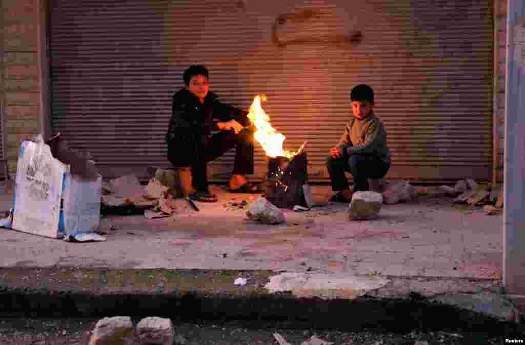 Boys warm up next to a fire outside a building in the Ain Tarma neighborhood of Damascus, February 5, 2013.