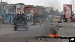Kendaraan polisi melewati sampah yang dibakar dalam protes-protes di Kinshasa, Republik Demokratik Kongo (20/12). (AP/John Bompengo)