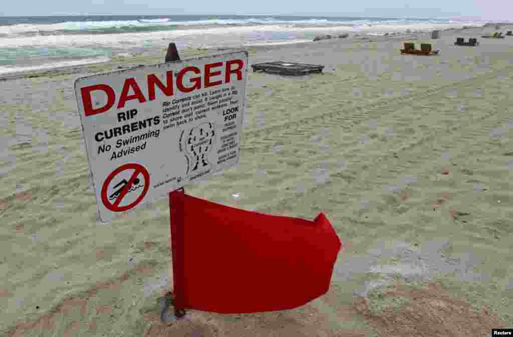 A red flag flies after lifeguards closed the area for swimming because of dangerous rip currents, as winds from Hurricane Sandy began to affect weather in Deerfield Beach, Florida, October 25, 2012.