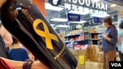 香港市民丁小姐在沙田一間阿布泰分店排隊約40分鐘,購買阿布泰獨家發售,2019年釀製、貼上象徵自由的黃絲帶及香港加油標貼的紅酒 (美國之音湯惠芸)