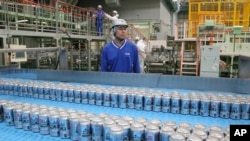FILE - Asahi Breweries plant manager Shinichi Uno watches the production line at an Asahi Breweries factory in Moriya near Tokyo, May 29, 2017.