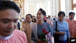 Myanmar opposition leader Aung San Suu Kyi, center, arrives to attend a regular session of the lower house of parliament, Nov. 16, 2015.