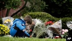 """Një fëmijë duke vendosur lule tek sinagoga """"Pema e Jetës"""", në qytetin Pittsburgh"""