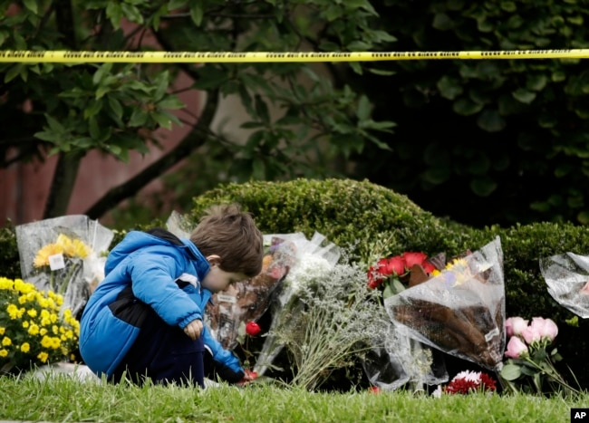 Gideon Murphy places a flower at the Tree of Life Synagogue in Pittsburgh, Sunday, Oct. 28, 2018.