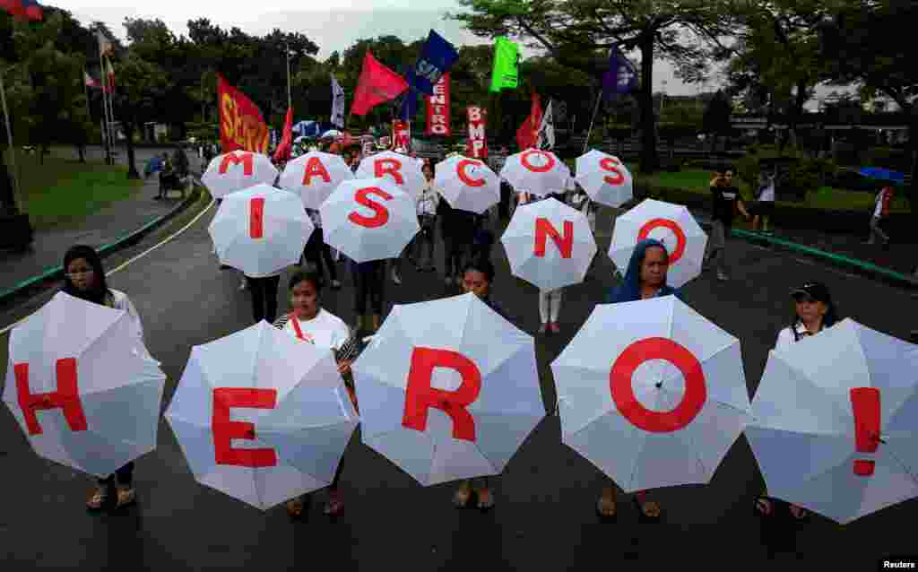 "Protesters display umbrellas spelling out ""Marcos is no Hero"" as they join hundreds of protesters denouncing the planned burial of late dictator Ferdinand Marcos at the Libingan ng mga Bayani (Heroe's Cemetery) during a protest at a park in metro Manila, Philippines."