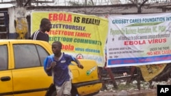 People pass by Ebola virus health warning signs, in the city of Monrovia, Liberia, Aug. 17, 2014.