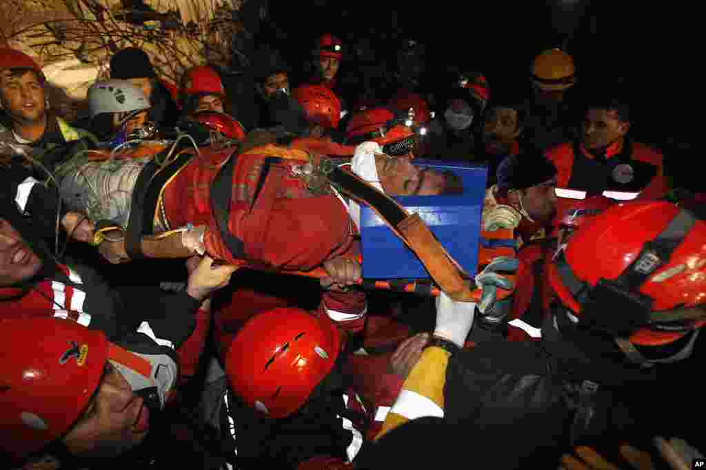 Rescue workers carry Imdat, 18, from a collapsed building after surviving for more than 100 hours, in Ercis, near the eastern Turkish city of Van, October 27, 2011. (Reuters)